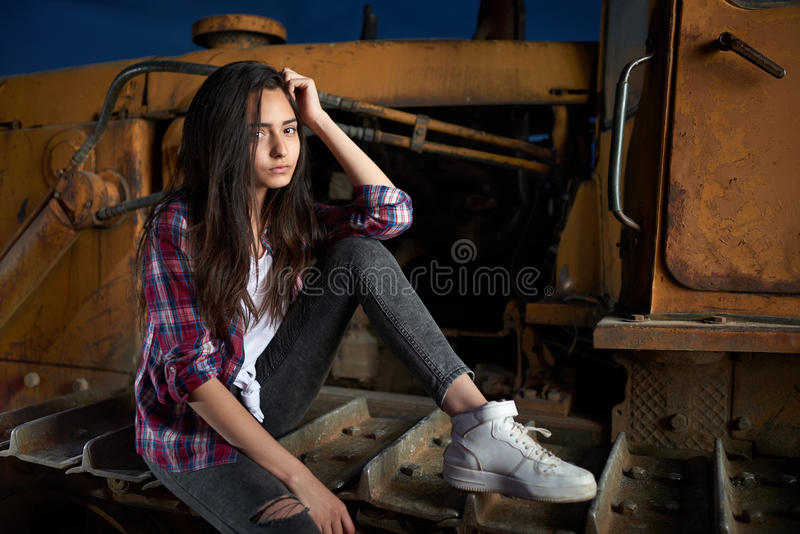 Belle fille de l'adolescence s'asseyant sur un vieux tracteur photographie stock libre de droits