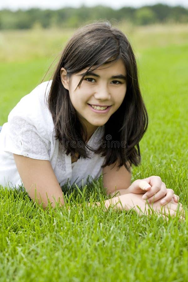 Belle fille de l'adolescence se trouvant sur l'herbe image stock