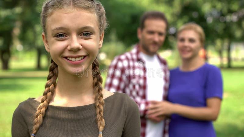 Belle fille de l'adolescence souriant sur le fond de ses parents heureux, famille de soin photos libres de droits