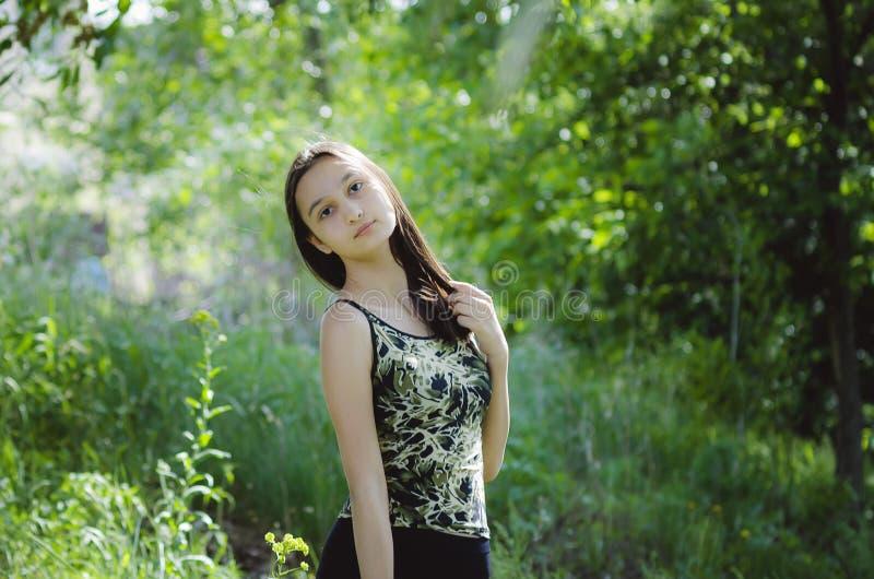 Belle fille de l'adolescence sur un fond vert d'arbre images libres de droits