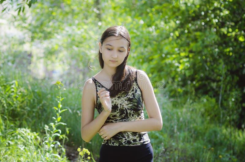 Belle fille de l'adolescence sur un fond vert d'arbre photos stock