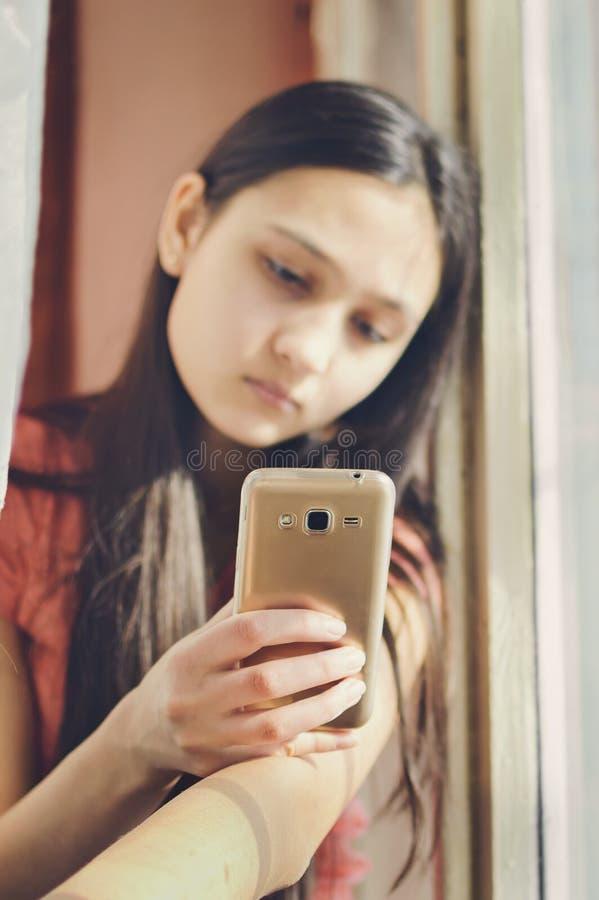 Belle fille de l'adolescence tenant un téléphone portable Style de mode de vie image stock