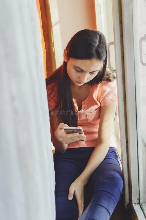Belle fille de l'adolescence tenant un téléphone portable Style de mode de vie photographie stock libre de droits
