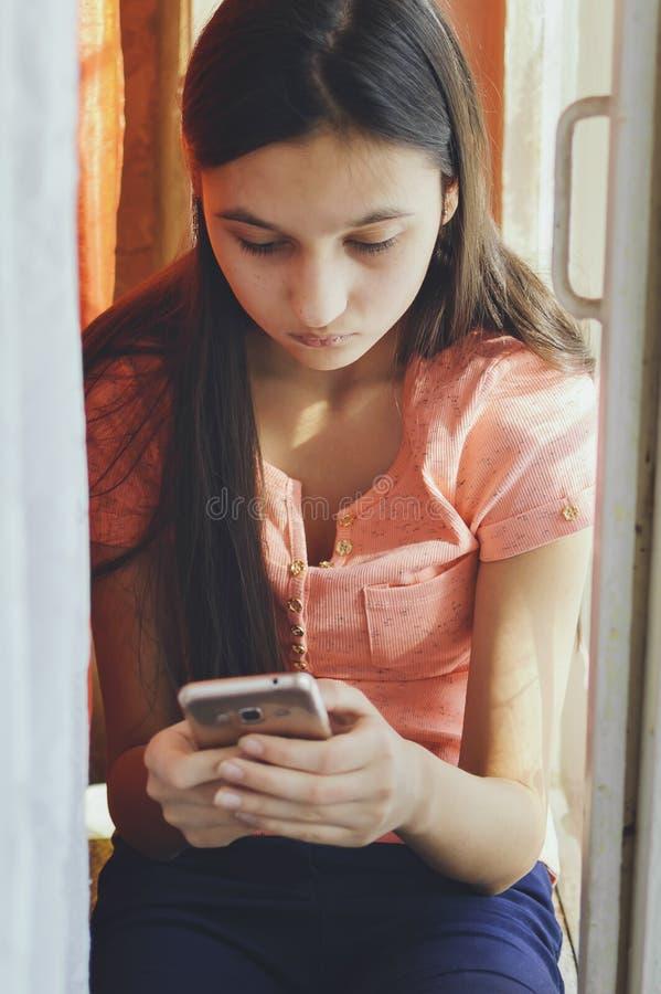 Belle fille de l'adolescence tenant un téléphone portable Style de mode de vie image libre de droits