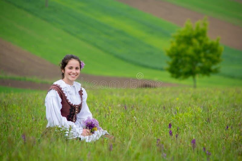 Belle fille de la Roumanie et costume traditionnel dans l'heure d'été images libres de droits