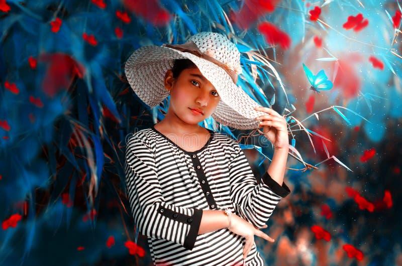 Belle fille de mannequin avec la pose extérieure de grand chapeau pour la caméra image libre de droits