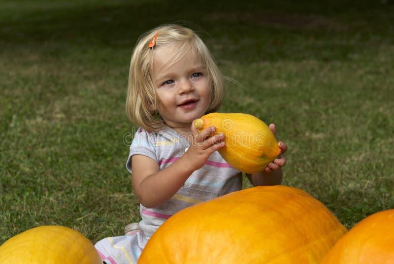 Belle fille de petit enfant ayant l'amusement avec l'agriculture sur la correction organique de potiron images stock
