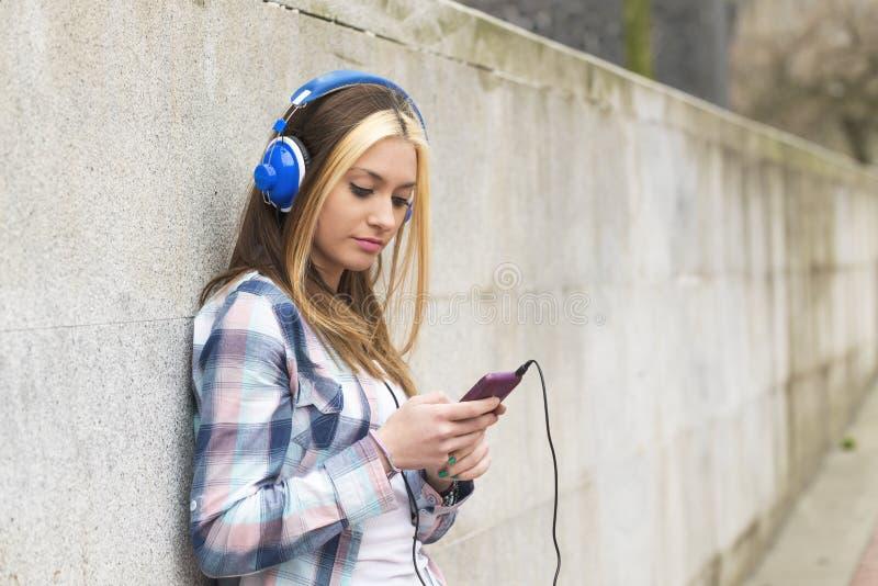 Belle fille de portrait urbain avec la musique de écoute d'écouteurs images libres de droits