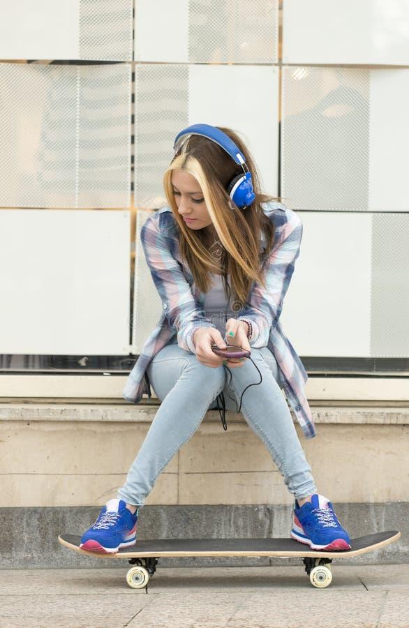 Belle fille de portrait urbain avec la musique de écoute d'écouteurs photo libre de droits