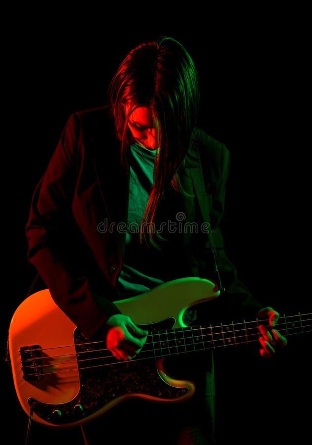 Belle fille de roche jouant la guitare basse image stock