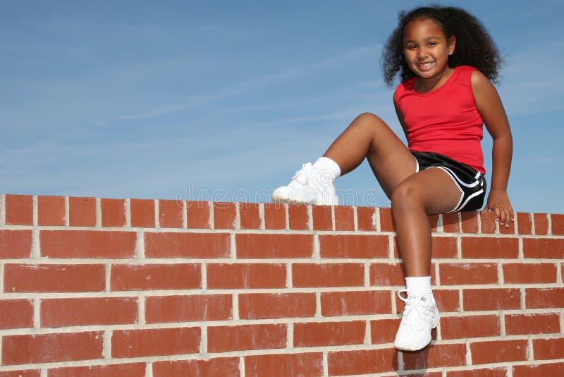 Belle fille de sept ans sur le mur de briques image stock