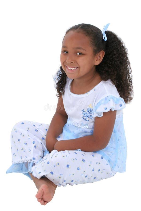 Belle fille de six ans s'asseyant dans des pyjamas au-dessus de blanc photos libres de droits