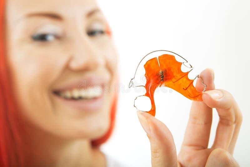 Belle fille de sourire avec l'arrêtoir pour des dents, plan rapproché image libre de droits