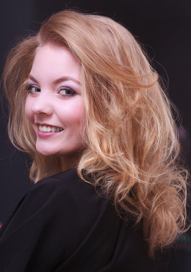 Belle fille de sourire avec les cheveux onduleux blonds par le coiffeur dans le salon de beauté images stock