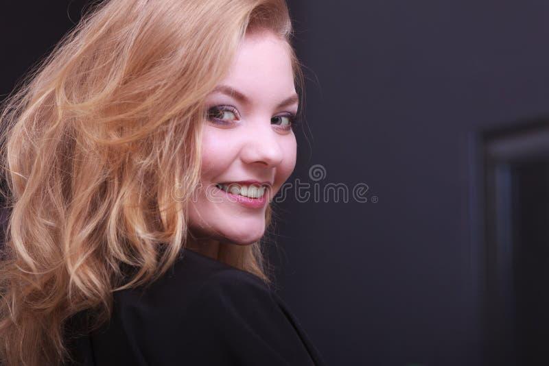 Belle fille de sourire avec les cheveux onduleux blonds par le coiffeur dans le salon de beauté photo libre de droits