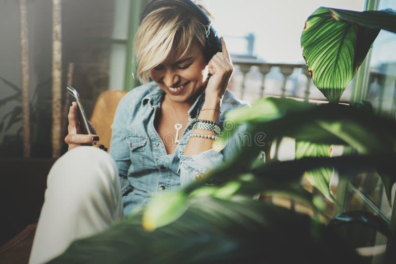 Belle fille de sourire détendant à la maison, vêtements sport de port, jouant la musique, utilisant le smartphone et les livres a images libres de droits