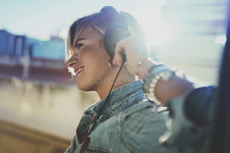 Belle fille de sourire détendant à la maison, vêtements sport de port, jouant la musique, utilisant le smartphone et les livres a image stock