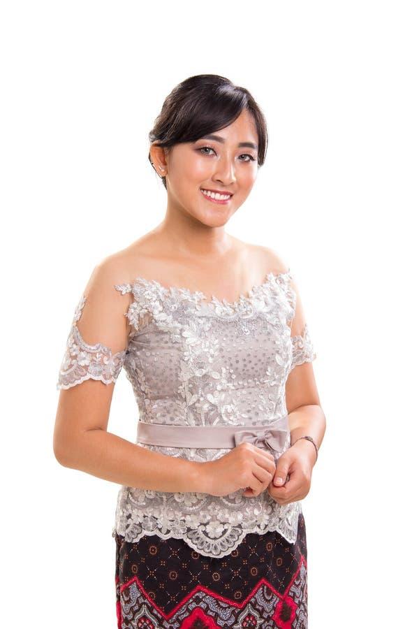 Belle fille de sourire d'Asie du Sud-Est utilisant les équipements à la mode modernes de Kebaya photographie stock libre de droits