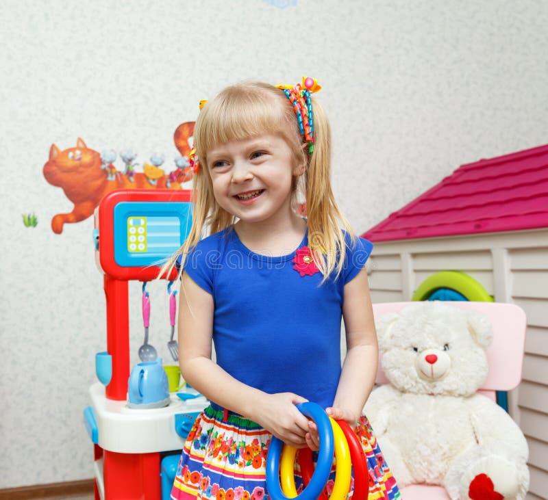 Belle fille de sourire jouant avec des jouets dans la garde image libre de droits