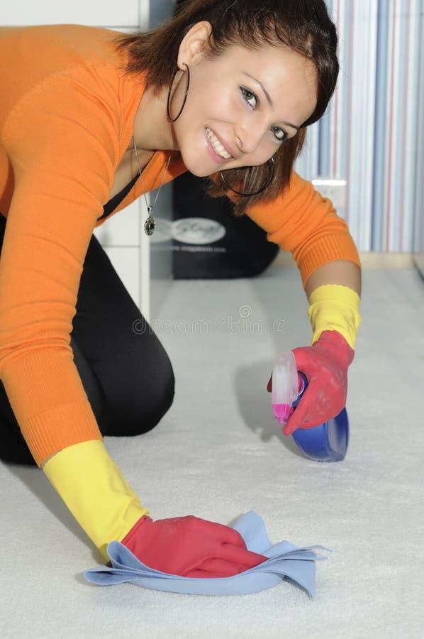 belle fille de sourire nettoyant la maison image stock