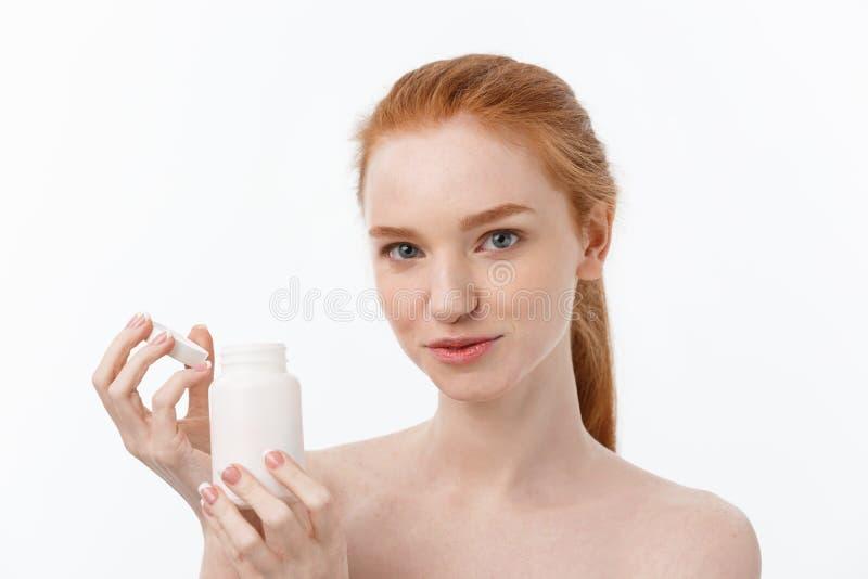 Belle fille de sourire prenant le médicament, tenant la bouteille avec des pilules Pilule femelle heureuse saine de consommation  image libre de droits