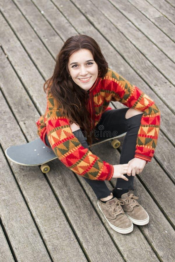 Belle fille de sourire s'asseyant sur la planche à roulettes, mode de vie urbain Co photo libre de droits
