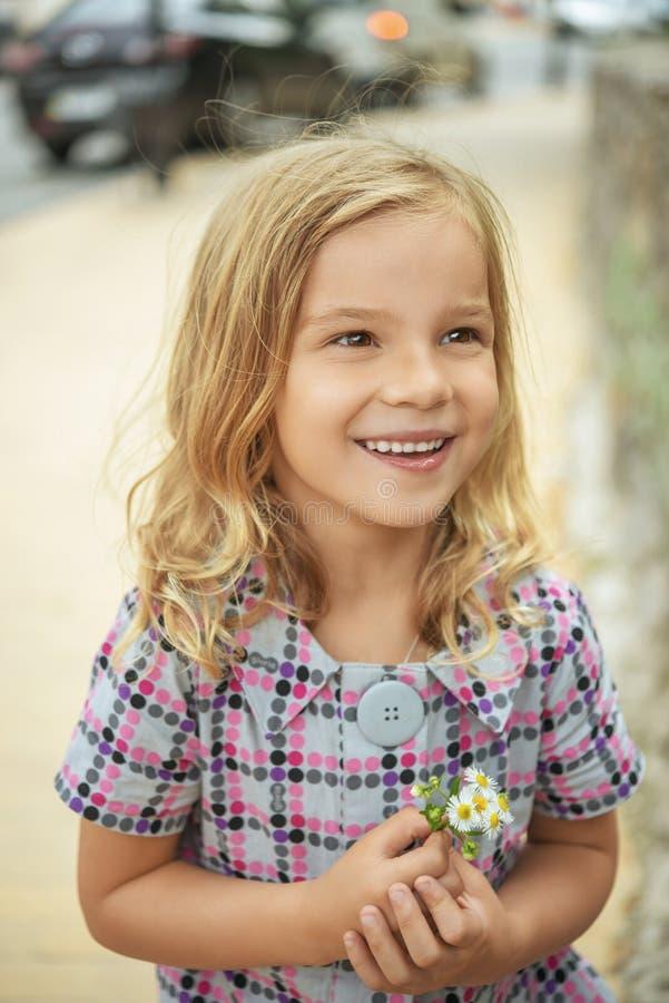 Belle fille de sourire tenant la fleur images stock