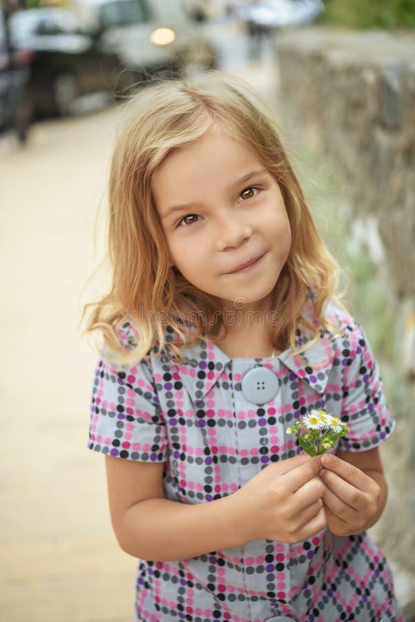 Belle fille de sourire tenant la fleur image stock