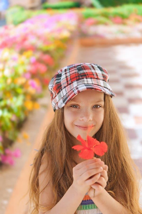 Belle fille de sourire tenant la fleur rouge photos libres de droits