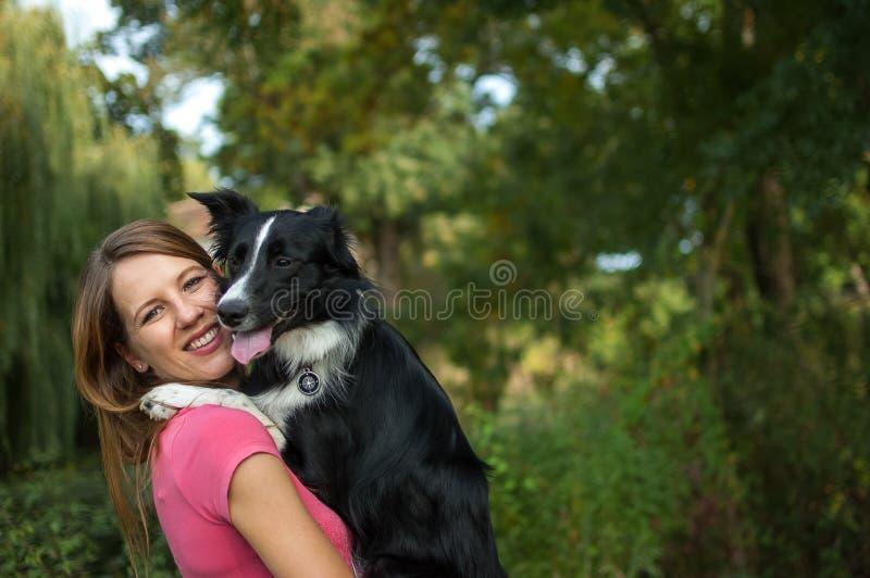 Belle fille de sourire tenant son chien blanc et noir sur des mains pendant le jour d'été photographie stock libre de droits