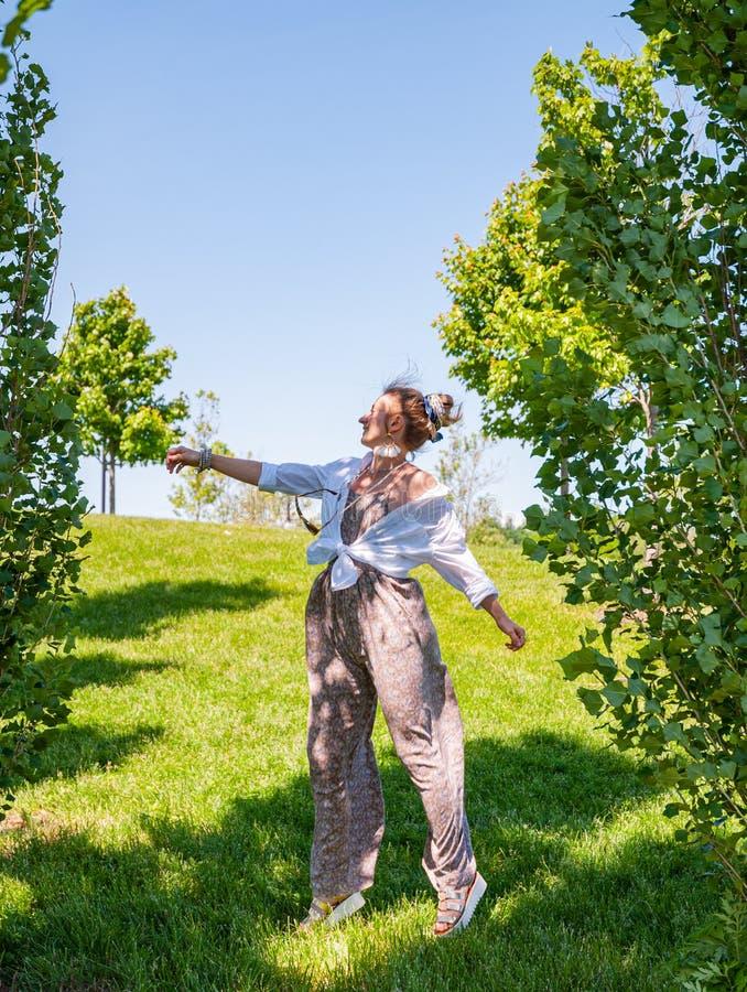 Belle fille de style de boho appr?ciant la libert? un jour ensoleill? Femme gaie sautant sur une herbe verte photo libre de droits
