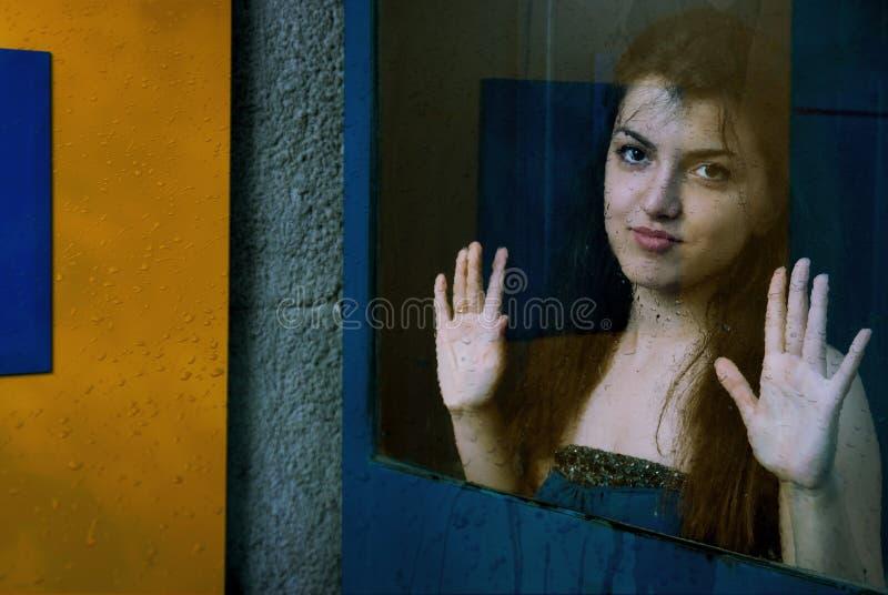 Belle fille derrière le verre sous la pluie photographie stock