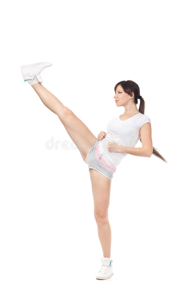 Belle fille donnant un coup de pied avec la jambe d'isolement sur le fond blanc image libre de droits