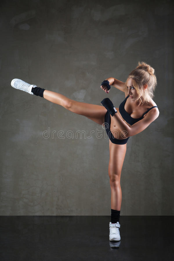 Belle fille donnant un coup de pied avec la jambe sur gris-foncé image stock