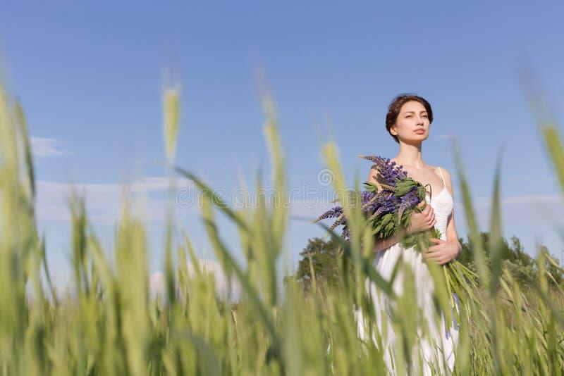 Belle fille douce avec des cheveux de tresse dans un bain de soleil blanc d'été marchant dans un domaine avec un bouquet des fleu photographie stock