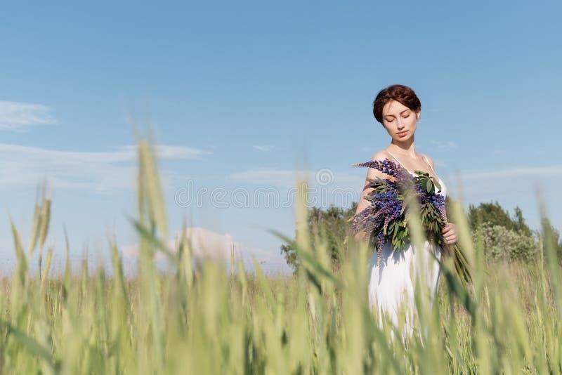 Belle fille douce avec des cheveux de tresse dans un bain de soleil blanc d'été marchant dans un domaine avec un bouquet des fleu images stock
