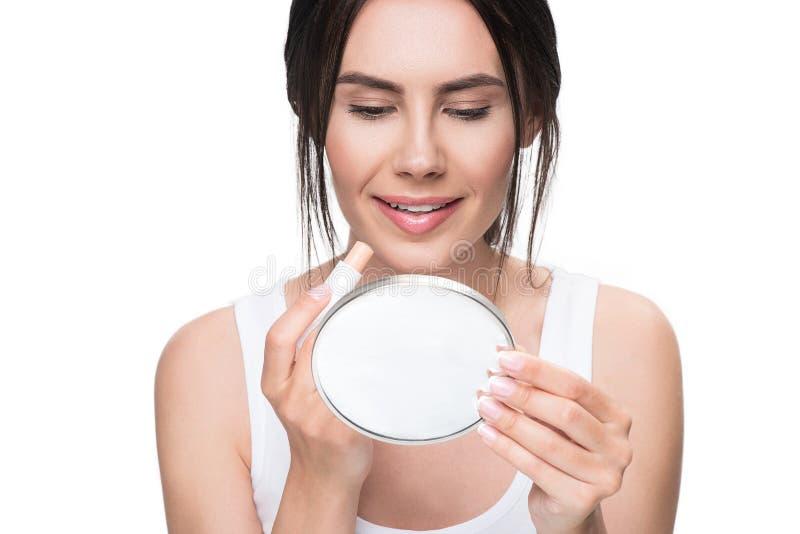 Belle fille employant le bâton de pommade pour les lèvres parfaitement photographie stock libre de droits