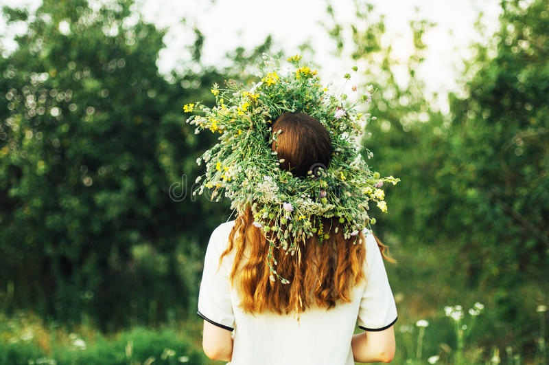 Belle fille en guirlande des fleurs dans le pré le jour ensoleillé Portrait de la jeune belle femme portant une guirlande des fle photos stock