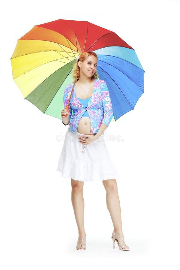 Belle fille enceinte avec un parapluie d'arc-en-ciel photo stock
