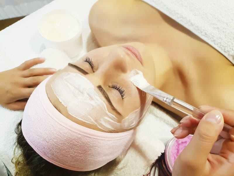 Belle fille, esthéticien cosmétique de masque en bonne santé de la procédure de cosmétologie de soins de la peau de crème hydrata photographie stock libre de droits