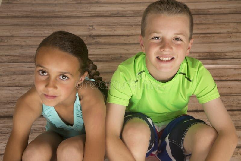 Belle fille et garçon s'asseyant sur le plancher en bois recherchant photos libres de droits