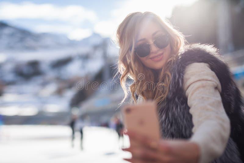 Belle fille faisant un téléphone portable de selfie à la patinoire photo stock