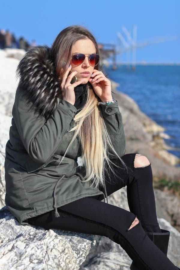 Belle fille Femme heureuse marchant et parlant au téléphone sur la plage avec la mer à l'arrière-plan photo stock