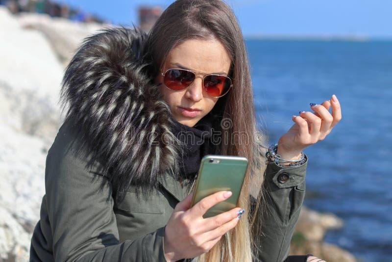 Belle fille Femme heureuse regardant au téléphone sur la plage avec la mer à l'arrière-plan photographie stock