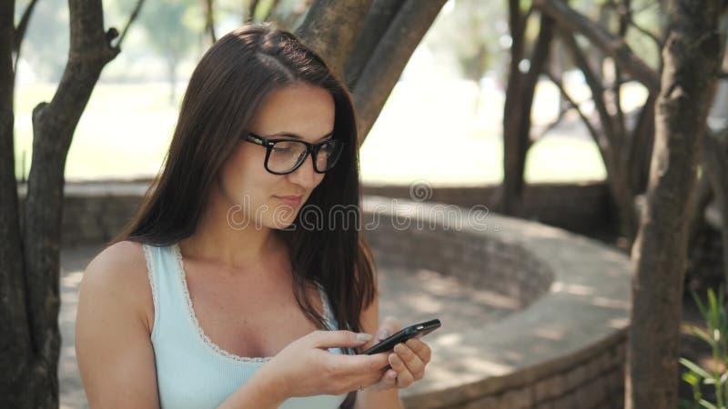 Belle fille gaie avec Smartphone se reposant en parc sur un banc sur Sunny Day, concept en ligne d'achats image stock