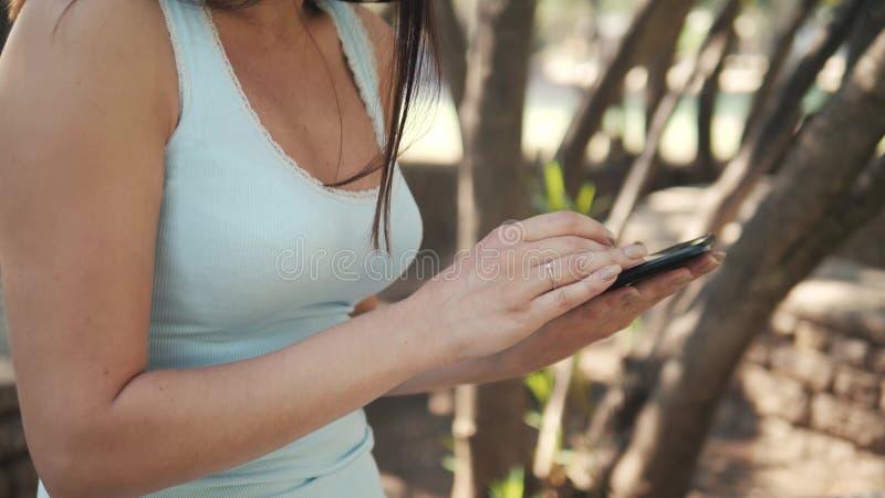 Belle fille gaie avec une tablette se reposant en parc sur un banc sur Sunny Day, concept en ligne d'achats photos stock