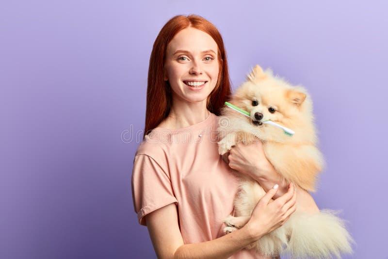 Belle fille gaie heureuse tenant un chien avec une brosse à dents sur ses dents images libres de droits