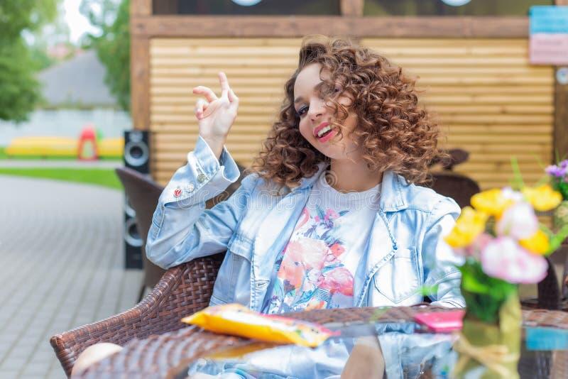 Belle fille gaie mignonne dans une robe lumineuse avec les cheveux bouclés et le maquillage lumineux se reposant à un café extéri images libres de droits