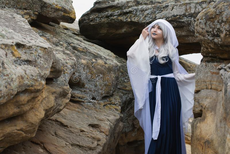 Belle fille habillée en tant qu'elfe dans une robe blanche Pose sur les pierres image libre de droits