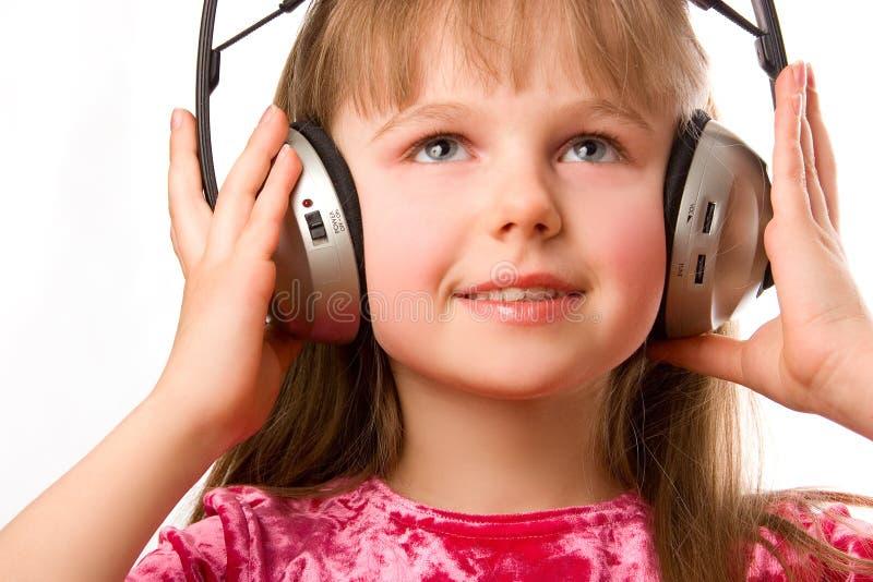 Belle fille heureuse avec des écouteurs images stock